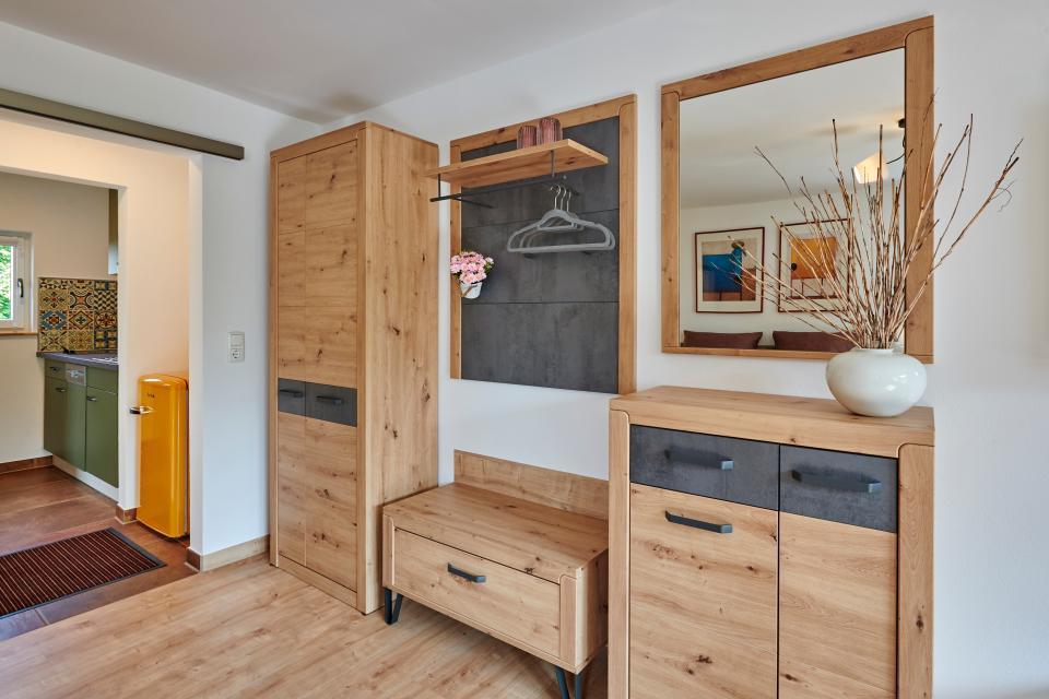 Viel Platz in der Garderoben-/Schrankkombi, der Blick geht durch den Gang mit Kühlschrank hinüber in die Küche.