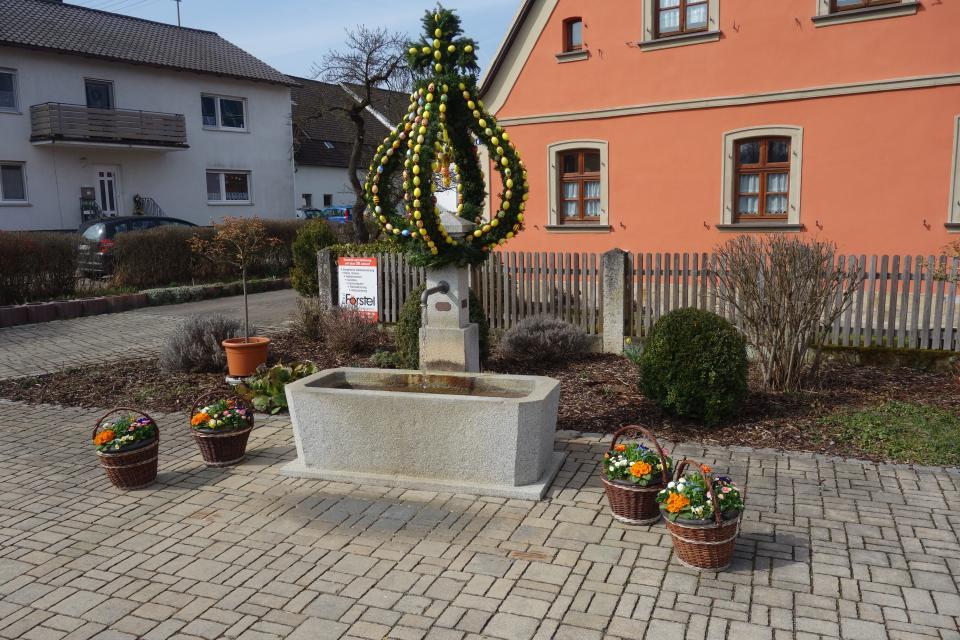 """Die Osterkrone auf dem Dorfbrunnen wurde von der Roßdorfer Dorfgemeinschaft unter Beachtung der Coronavorschriften """"im Homeoffice"""" geschmückt"""