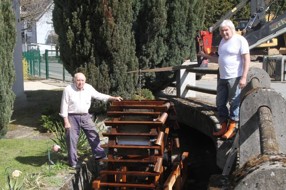 """Das Werk ist vollendet: Mit einem Frontlader hoben die """"Bauherren"""" Konrad Kestler (links) und Adolf Hasenkopf das neue Wasserschöpfrad in den Zeegenbach."""