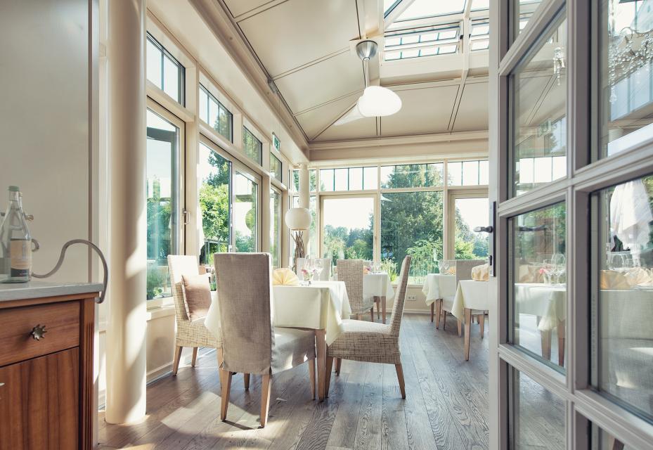 Im Wintergarten des Restaurant speisen Gäste mit Blick auf den umliegenden Schlossgarten
