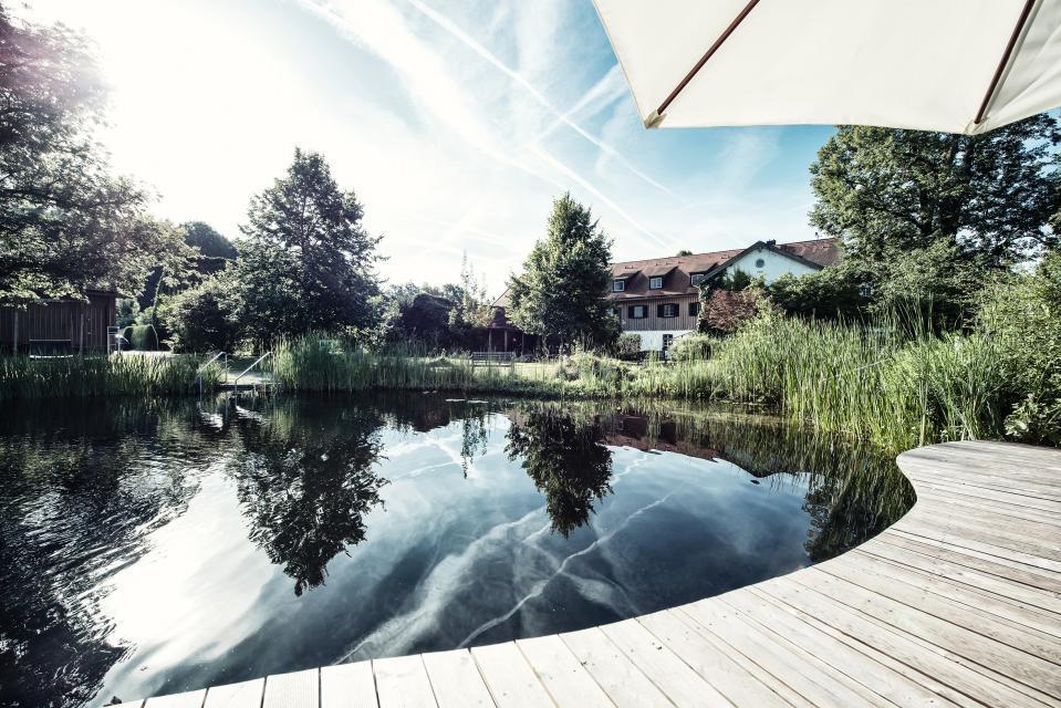 Der nach Feng-Shui ausgerichtetete Naturbadeteich des Biohotels ist nicht nur schön anzusehen, sondern lädt Gäste zum Schwimmen ein